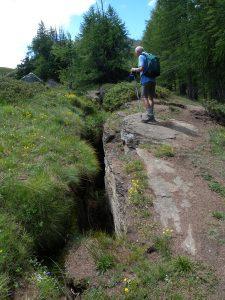 1.Apertura di un trench lungo la cresta rocciosa che sovrasta la bassa Val di Rhêmes, versante sinistro. La roccia è calcescisto (metasedimento oceanico) con giacitura immergente a W (destra nella foto) dove si stende il bosco verso Les Combes d'Introd.