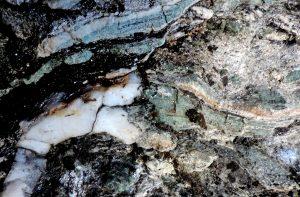 04. Noduli e lenticelle di giadeite strettamente associata a quarzo sulle pareti rocciose sotto Breil.
