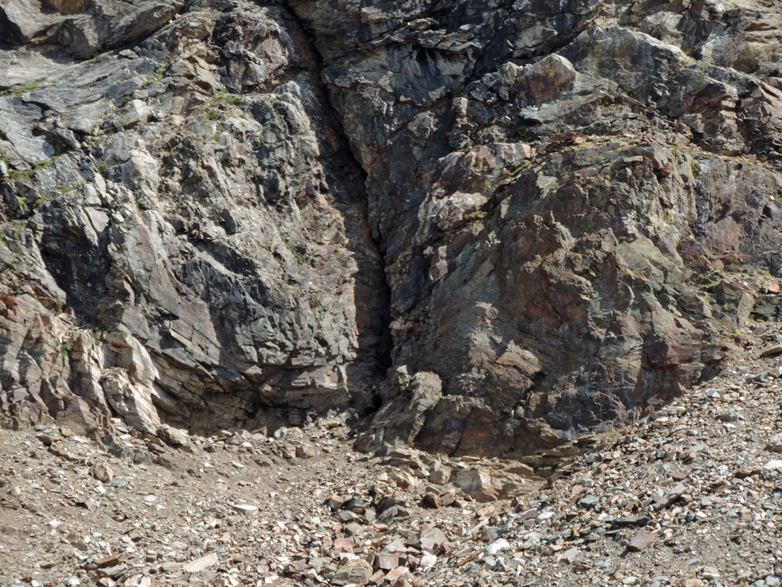 02. L'imbocco della galleria si apre alla base di una lunga fessura verticale nella bancata rocciosa.