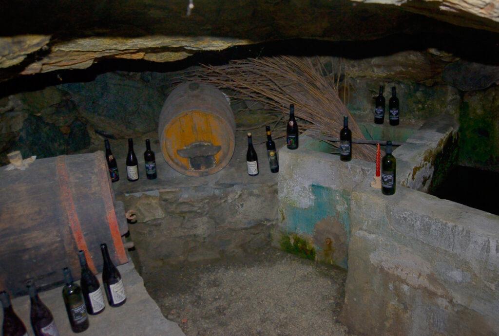 """Conservazione del vino Donnas DOC in un barmet sotto le vigne di Rovarey. A poca profondità sotto la colata detritica, il vano si apre nella roccia locale della DGPV che copre l'intero versante.zione dei """"barmet"""" ha impegnato Ilda per parecchio tempo. Questo si trova in un vigneto di Rovarey (Donnas)."""