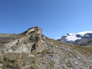18. Schistes lustrés et métabasites du Combin en lits alternés, impliqués dans un pli. Au fond le Mont Rose.