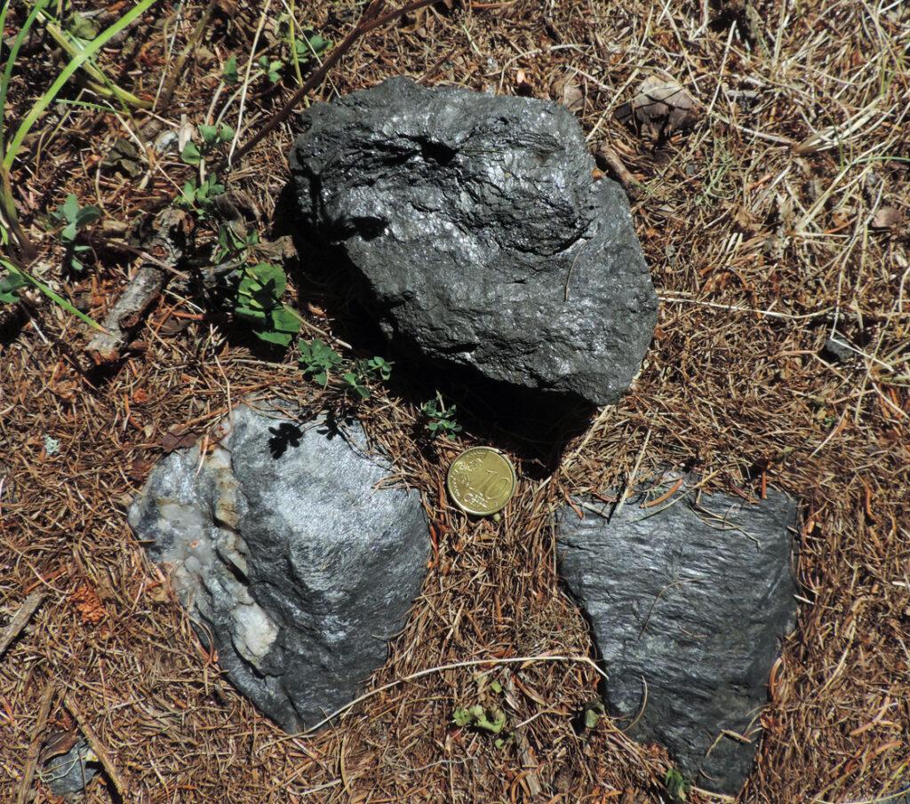 """02. Caduti dai vagoncini, ecco tre campioni delle rocce locali: l'antracite sopra, e due esempi di sterile, delle argilliti carboniose o """"scisti neri"""" con un livello conglomeratico a ciottolini di quarzite."""