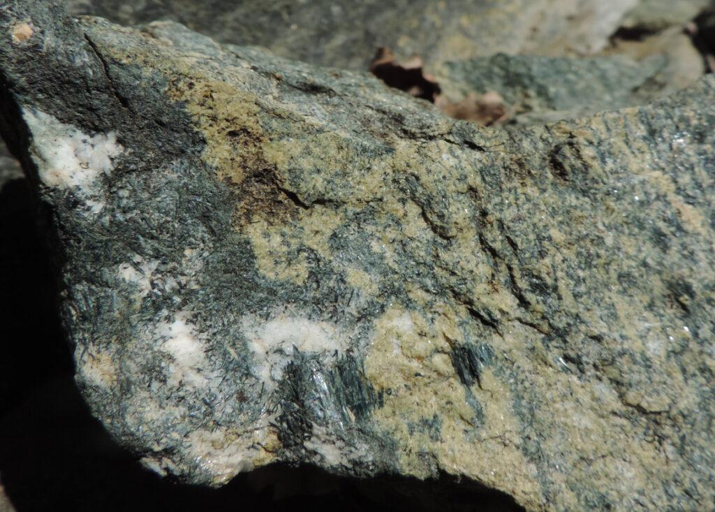 La balconata percorsa dal sentiero è sostenuta da rocce derivate da magmi iniettati nel fondale dell'antico oceano alpino, poi trasformate ad alta pressione con anfibolo blu ed epidoto (giallino).