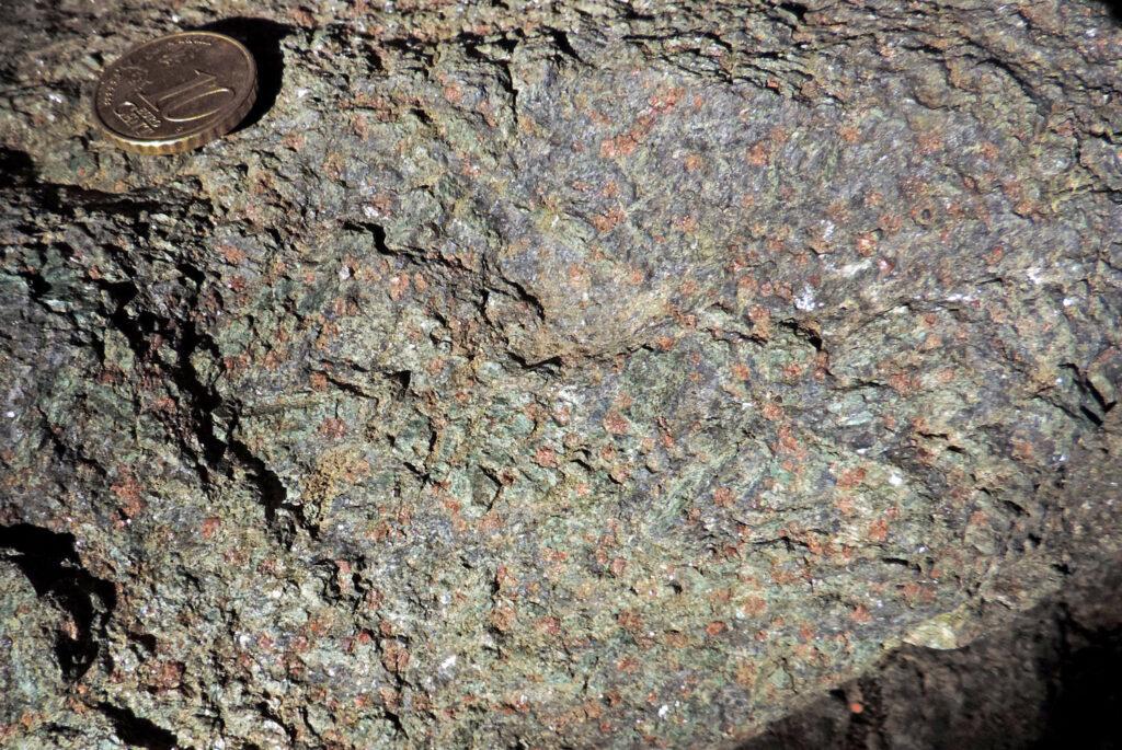 Eclogite della Torre di Pramotton. Sullo sfondo verde della giadeite (pirosseno sodico) si distinguono i cristalli allungati dell'anfibolo blu (glaucofane) e quelli tondi del granato.