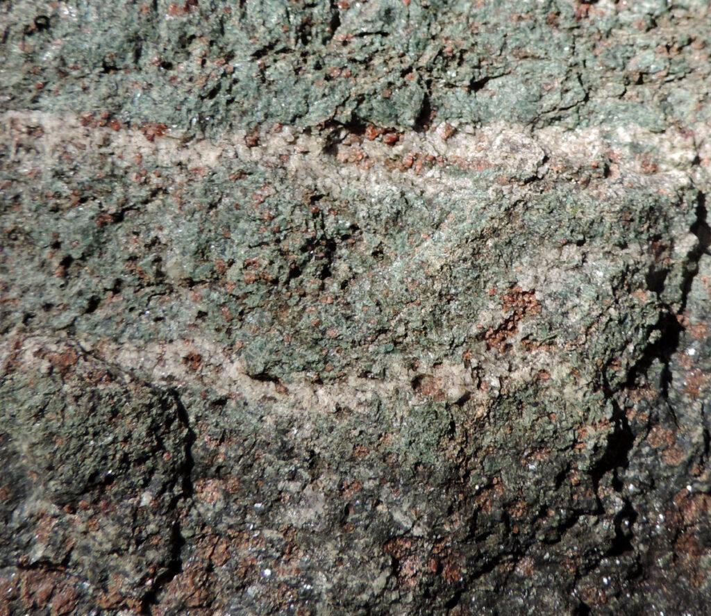 Ancora un'eclogite alla Torre di Pramotton. Qui un sottile livello deformato durante il processo metamorfico vivacizza cromaticamente e geometricamente la massa rocciosa composta da granato e pirosseno sodico (giadeite-onfacite).