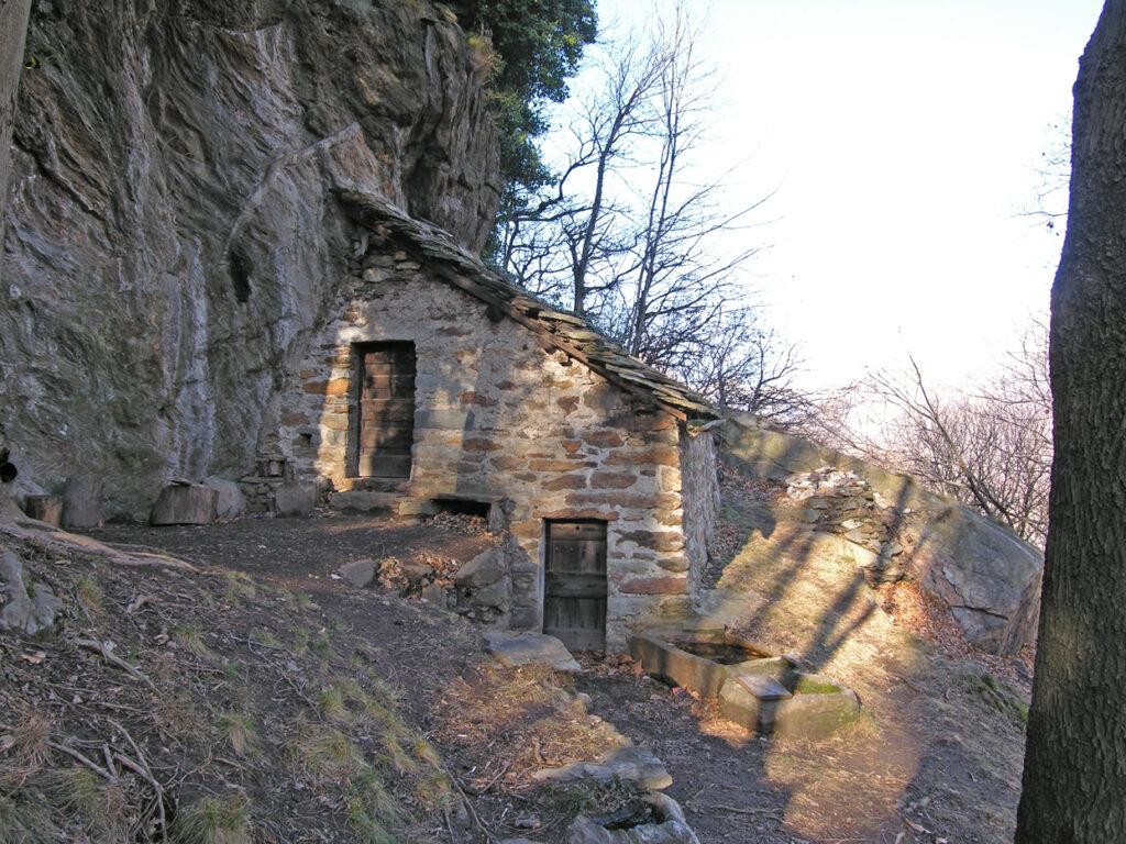 A metà salita appare sulla destra il piccolo edificio addossato alla parete rocciosa. Ai suoi piedi notare le due vasche monolitiche.